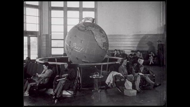 1940s: San Francisco, waiting room, people sit around globe showing United States, Pacific Ocean. Men stand in line at ticket counter.