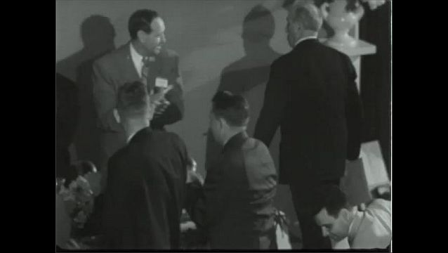 1940s: UNITED STATES: GM dinner and awards ceremony. Men applaud at dinner table. Man stands up. Men shake hands. Robert Moses wins award.