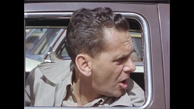 1940s: UNITED SATES: man gets frustrated in traffic jam. Man smokes cigarette. Man shouts through car window. Man looks at watch. Police Officer in traffic jam.