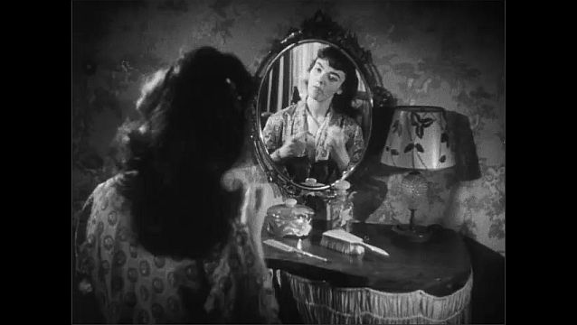 1940s: Brunette teenage girl in robe sits at her vanity and brushes her hair. Girl ties her hair back and smiles at herself in the mirror.