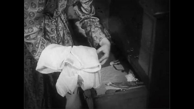 1940s: Brunette teenage girl in robe removes neatly folded clothing from her dresser drawer. Girl opens her closet and pulls out an outfit.