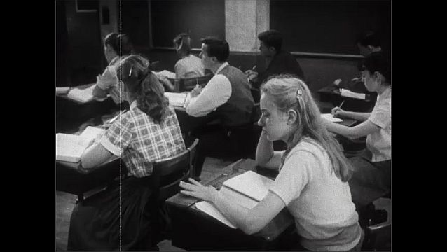 1940s: Messy blonde girl looks glum sitting at her desk. Girl drums her fingers on the desk and her classmates turn to look.