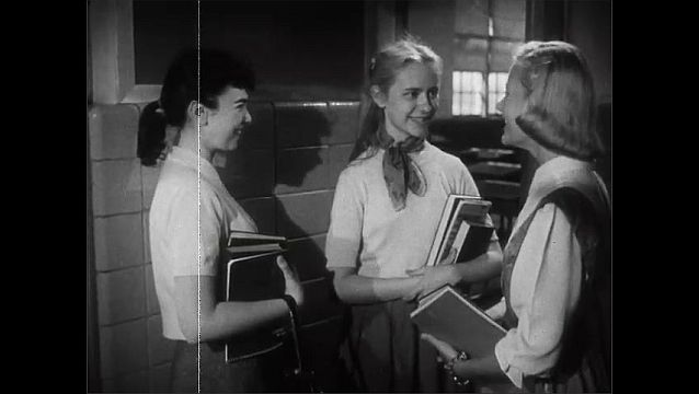 1940s: Messy blonde girl and tidy brunette chat in the hallway of school with a third girl who invites them over. The brunette and the blonde both agree and chat excitedly.