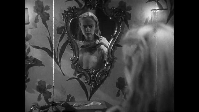 1940s: Messy blonde girl looks into her mirror and removes the scarf from around her neck, showing her stained sweater.