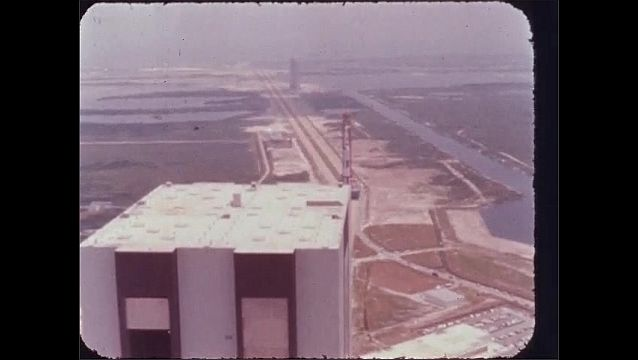 1960s: Building.  Rocket on launch pad moves down dirt road.