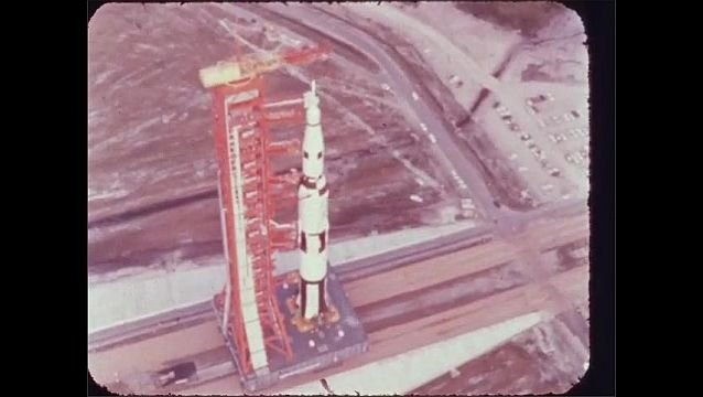 1960s: Rocket on launch pad moves down dirt road.  Parking lot.
