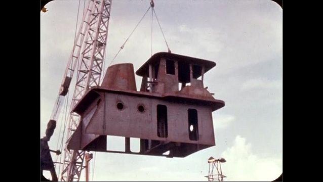 1960s: Crane lowers boat frame.