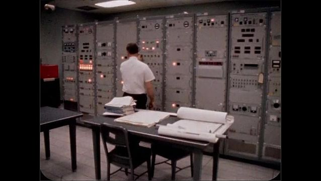"""1960s: Man holds sign reading """"MISSISSIPPI TEST FACILITY.""""  Man works on wall of computer equipment."""