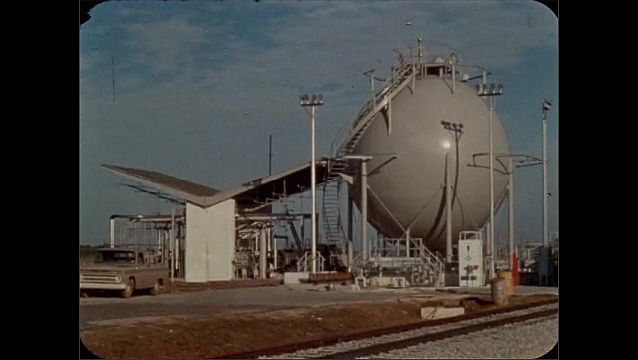 1960s: Train tracks.  Stairs lead to top of spherical storage tank.  Shelter.  Parked car.
