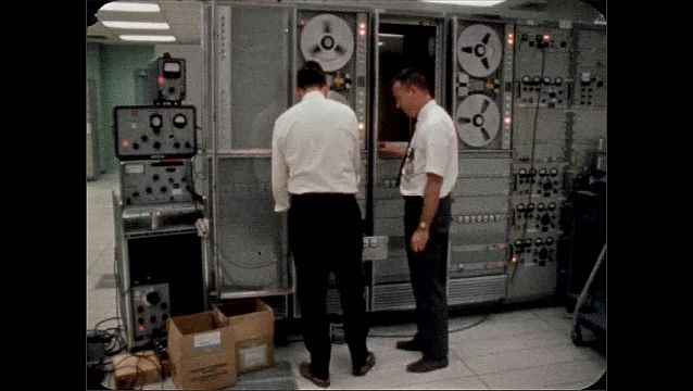 """1960s: Hand holds sign that reads """"MISSISSIPPI TEST FACILITY.""""  Men talk and work on machine.  Reels spin.  Computer."""