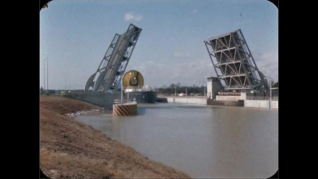 1960s: UNITED STATES: boat enters through open bridge.
