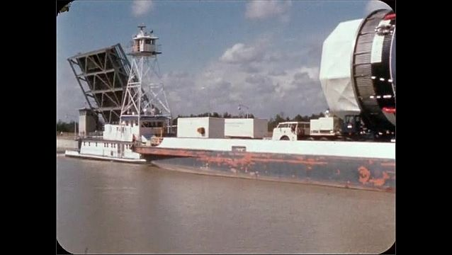 1960s: UNITED STATES: large metal structure transported along waterway by boat.