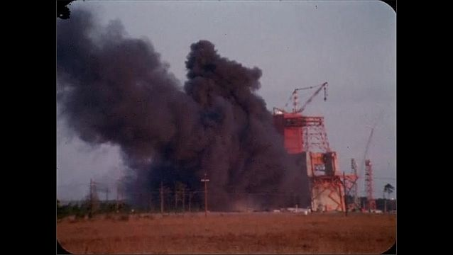 1960s: UNITED STATES: black smoke from test fire at NASA facility. Side view of fire.