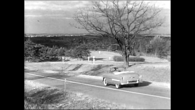 1950s: Car drives down road. Sign for Chevrolet Engineering Tests. Cars drive on road. Cars in showroom.