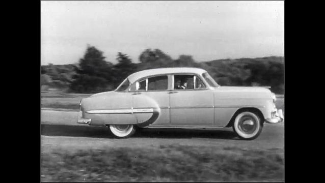 1950s: Man presses gas pedal. Car drives down road. Car stops at stop sign, continues driving.