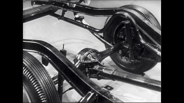 1950s: Car engine, frame, and transmission. Man walks around frame of car. Car in showroom.