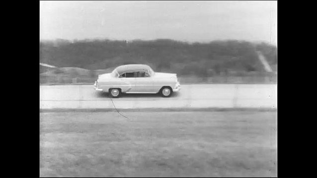 1950s: Car drives down road. Car drives with bicycle tire attached to rear end.
