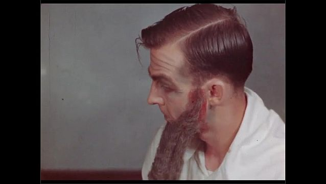 1950s: UNITED STATES: man sticks beard on face. Man attaches side burns on face.