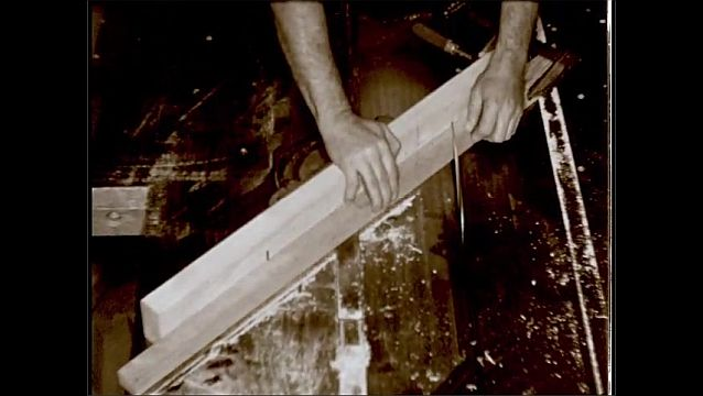 1950s: UNITED STATES: man cuts wood on saw. Fingers by saw.