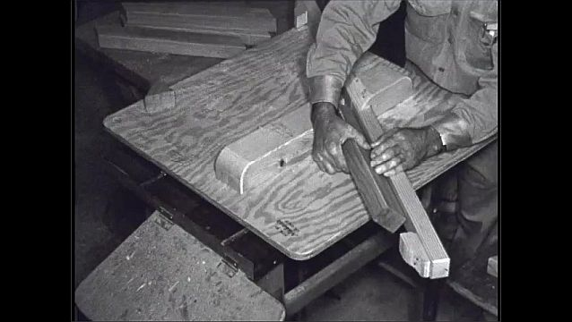 1950s: UNITED STATES: man cuts sections of wood on blade.