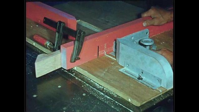 1950s: UNITED STATES: man slices wood on saw. Man adjusts grip on wood.