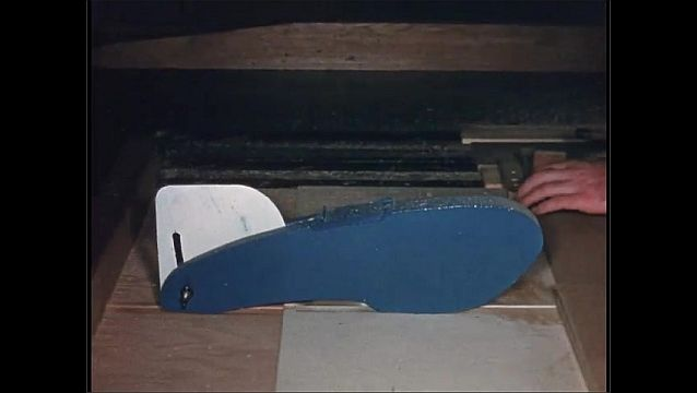 1950s: UNITED STATES: metal guard on saw. Man slides board towards saw.