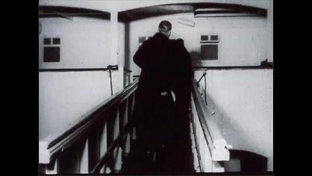 1950s: Man walks across deck of ship, walks down gangway.