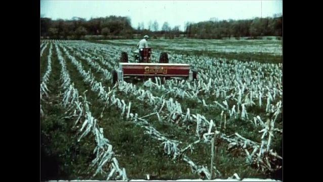 1950s: Man holds jar of dirt, talks. Man drives tractor across field. Plane dusts crops.