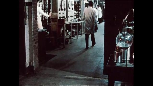 1950s: Man removes bottle of liquid from chemistry set-up, opens door, walks into large lab. Men in lab.