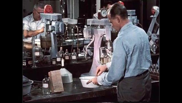 1950s: Man pours dirt into dish. Men examine dirt.