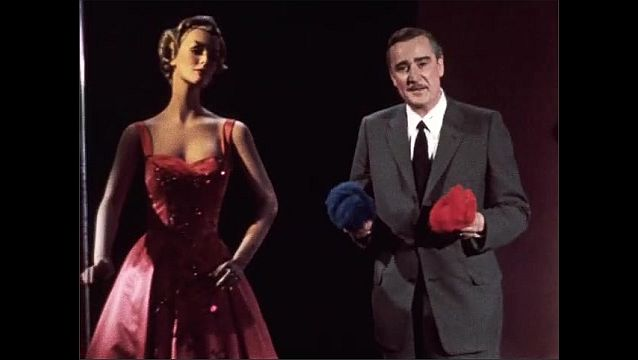1950s: Man in suit talks, picks up balls of colorful fibers. Man stands next to mannequin in dress.
