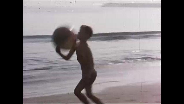1950s: Boy runs up to people on beach blanket, tussles with man, grabs ball, runs away. Boy runs down beach, plays with ball, runs into man. Man helps boy up.