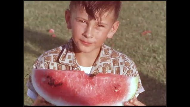 1950s: UNITED STATES: boy eats slice of water melon.