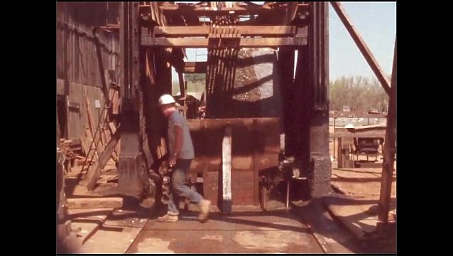 1950s: UNITED STATES: man by wood chipping machine