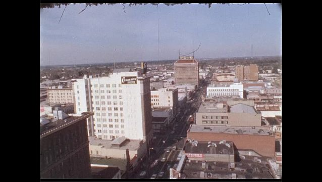 1950s: Aerial view of skyscrapers and buildings in downtown city.