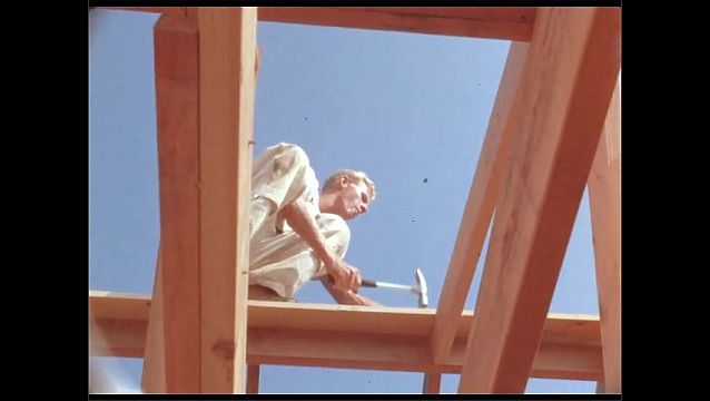 1950s: Man hammers nails into boards of new home construction.