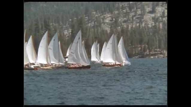 1950s: Teams of men pilot sail boats in regatta. Ships sail on forest lake.