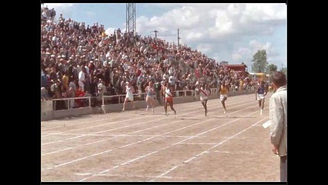 1950s: Spectators in stadium watch runners in footrace. Runners run on track in stadium.