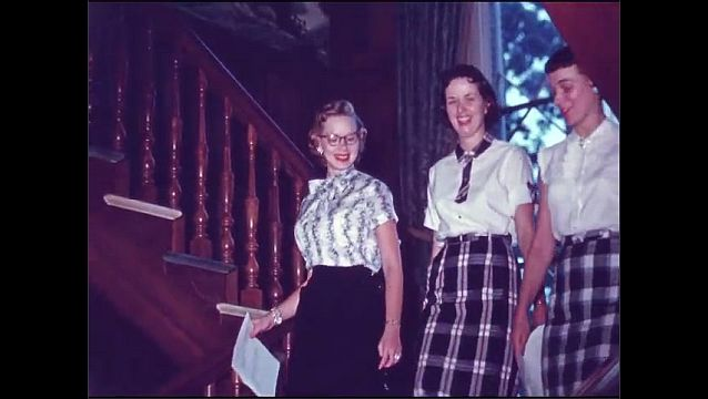 1950s: Paper printing in machine, pan to cards printing. People at office machines, woman hands file to man. Women walking down stairs. Men walking up stairs. Pan across people at desks.