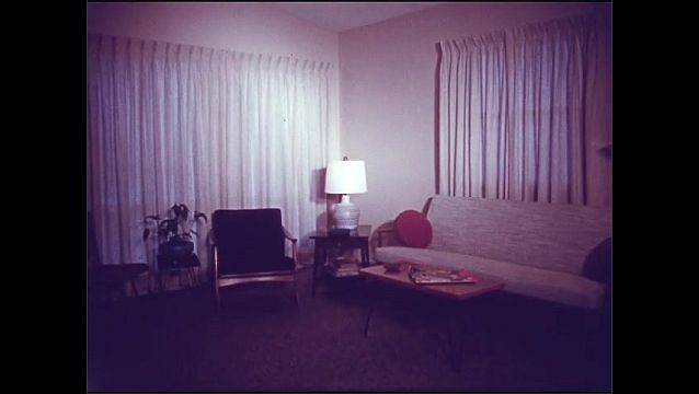 1950s: View of house, kids in yard. View of house. View of living room. Pan across room.