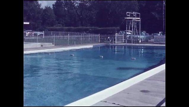 1950s: Woman by pool, pan to pool. Woman climbs into pool. Woman swims toward camera.