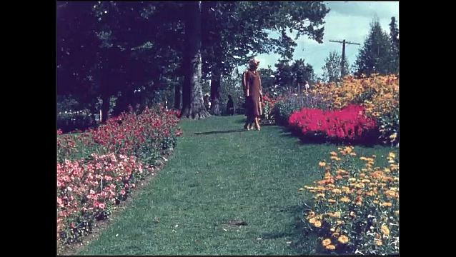 1950s: View of sign. Pan from sign to gate. Women walking by flowers. Women talking, look at flowers.
