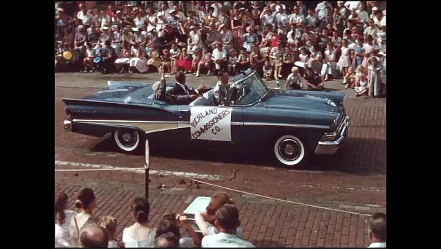 1950s: Shots of cars driving in parade, men waving.
