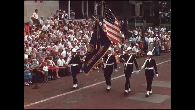 1950s: Antique car driving backwards in parade. Antique car driving. Marching band in parade. Soldiers marching with flags. Marching band in parade.