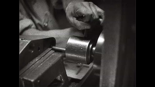 1930s: Worker machines engine part in automotive factory. Man operates drill press in machining factory.