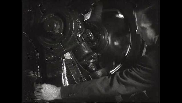 1930s: Flywheels on machinery spin and pull belts. Worker pushes button on machine control. Electrical turbine spins.