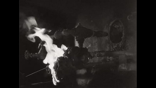 1940s: Machine rotating. Iris out, hands light torch, hold torch up to valve. Machinery lifting in front of fire.