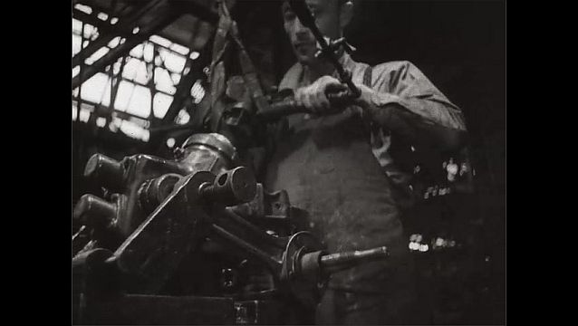1940s: UNITED STATES: man builds motor in factory. Man tightens bolts.