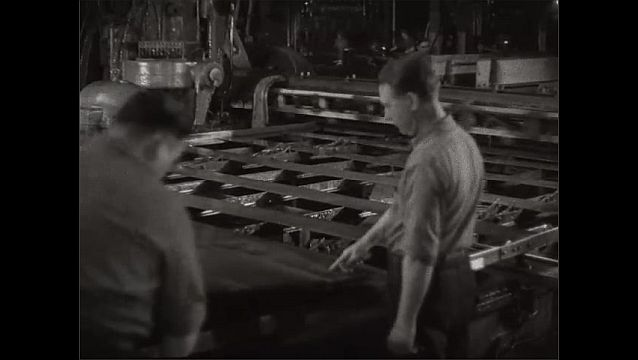 1940s: UNITED STATES: metal bars move along machinery. Man strikes metal with hammer. Man operates machinery.