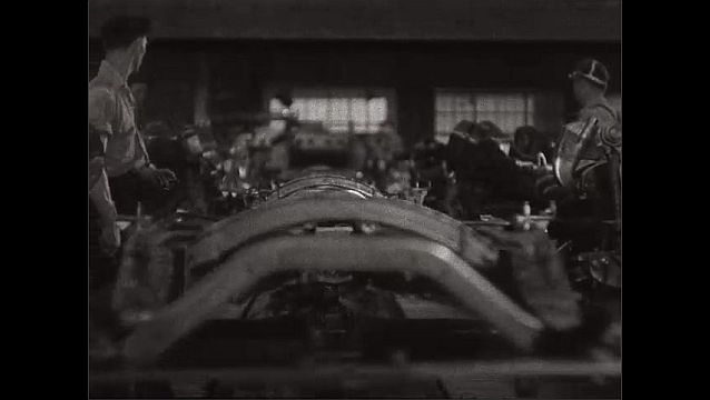 1940s: UNITED STATES: close up of hand on lever. Machinery and men work on production line. Man stands next to machinery on conveyor line.